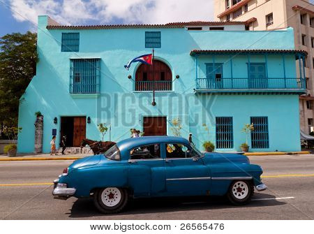 HAVANA - OCTOBER 23: Old  car in front of a building with the cuban flag October 23, 2010 in Havana. A tourist attraction by themselves, a  large number of vintage cars are still in use in Cuba.