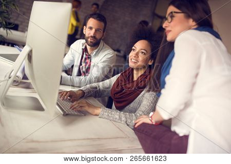 Young positive persons in office working together on modern computer