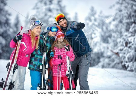 Skiing, winter, snow, sun and fun – smiling family enjoying holiday vacations together