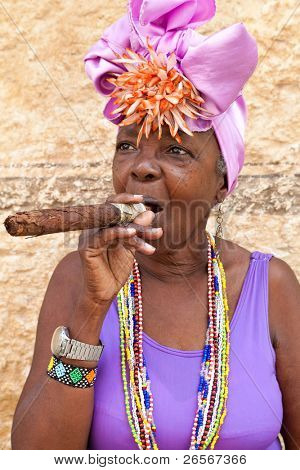 HAVANA-MARCH 28:Woman with typical clothes and a huge cuban cigar on March 28,2011 in Havana.People dress in a way that represents the cuban nationality can be found in the streets of Old Havana