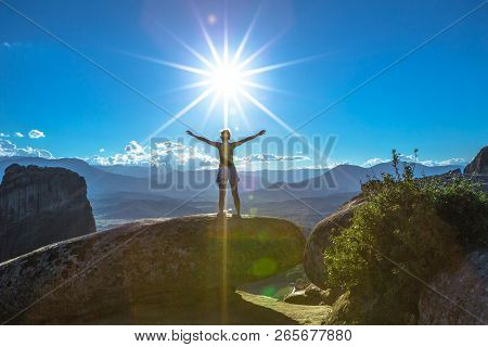 Girl Traveler With Open Arms At The Sun, On A Rock On Sunset In Meteora Landscape In Thessaly, Greec
