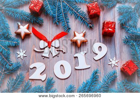 New Year 2019 background with 2019 figures, Christmas toys, blue fir tree branches and snowflakes. New Year 2019 still life
