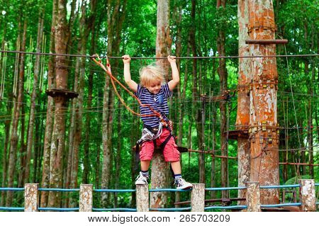 Brave Young Child In Safety Harness Climb High On Tree Tops, Pass Hanging Bridge Obstacle In Adventu