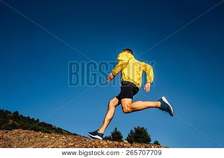 Male Athlete Runner In Yellow Jacket Run Uphill