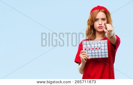 Young beautiful woman over isolated background holding menstruation calendar pointing with finger to the camera and to you, hand sign, positive and confident gesture from the front