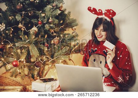 Beautiful Girl In Reindeer Antlers Holding Credit Card And Shopping Online, Sitting With Laptop At G