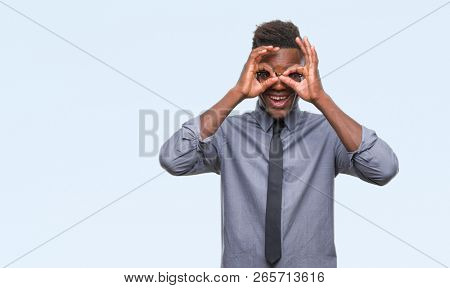 Young african american business man over isolated background doing ok gesture like binoculars sticking tongue out, eyes looking through fingers. Crazy expression.