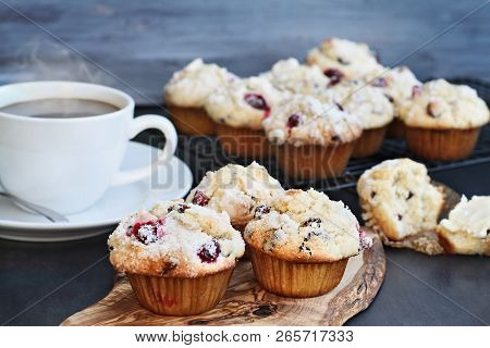 Cranberry Muffins On A Wood Cutting Board With More Cooling On A Bakers Rack. Extreme Shallow Depth