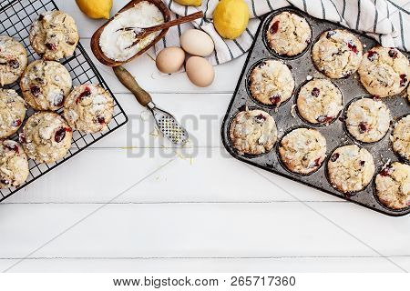 Cranberry Muffins In A Muffin Tin With Fresh Eggs, Sugar, Lemons And Lemon Zest Over A Rustic White