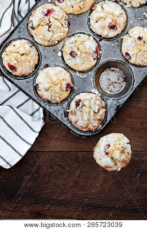 Cranberry Muffins  In A Muffin Tin With Kitchen Towel Over A Rustic Wood  Background. Free Space For