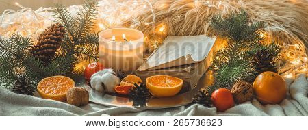 Cozy Winter Morning At Home. Book And Tangerines In A Winter Composition, Christmas Trees, Candles,
