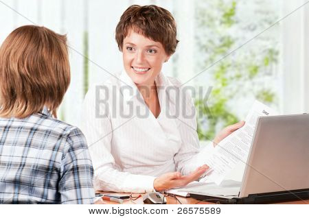 Beautiful  businesswoman working with contract and her client at office