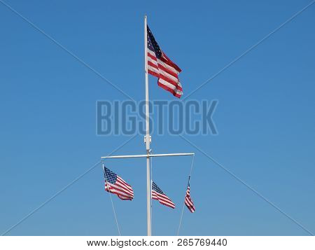 A Marina Flag Pole With American Flags Against Blue Sky. This Being In Texas, The Lower Bar Could Ha