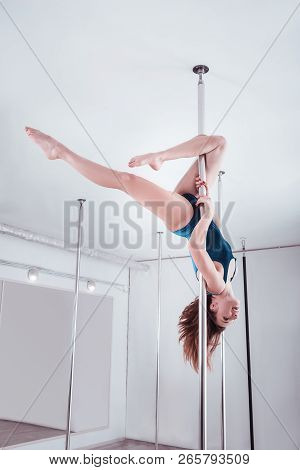 Slim Athletic Pole Dancer Dancing On Pole With Head Down