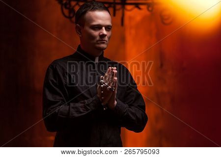 Young Catholic Praying Priest. Portrait Of Priest Next To The Candles Prays With His Hands Folded Ne