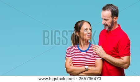 Middle age hispanic couple in love over isolated background with serious expression on face. Simple and natural looking at the camera.