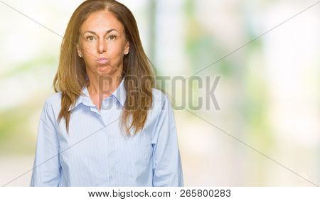 Beautiful middle age business adult woman over isolated background puffing cheeks with funny face. Mouth inflated with air, crazy expression.