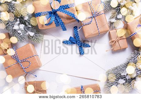 Empty Tag And Frame From Wrapped Christmas Presents And Fur Tree Branches With Bokeh Lights On  Whit
