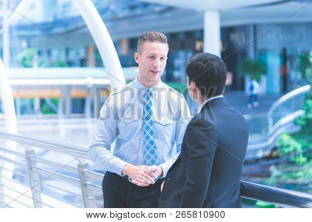 Two Business Men Are Talking In An Outdoor Train Station