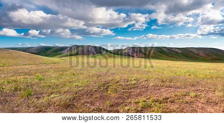 Panorama Hills In Sunny Day. Vista Scenic Idylic Landscape Hills Sun Through The Clouds Meadow