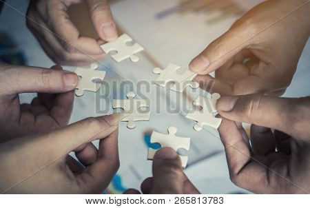Team Placing Six Puzzles Jigsaw Together For Team Concept
