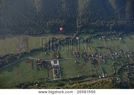 Aerial View Of Hot Air Balloons Flying Over Village