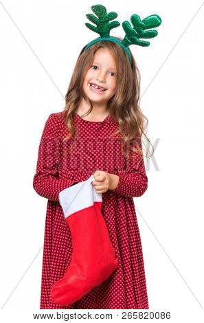 Portrait of caucasian girl with funny Christmas antlers of a deer. Happy schoolgirl, isolated on white background. Holiday concept - funny cute child holding Christmas sock.