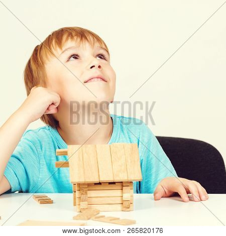 Little Boy Builds House From Wooden Blocks. My House Concept. Concept Of Dream Home And Mortgage Inv
