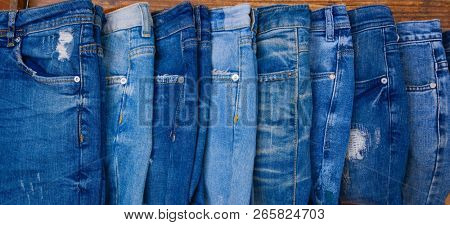 Various blue jeans on wooden background . Stack of jeans