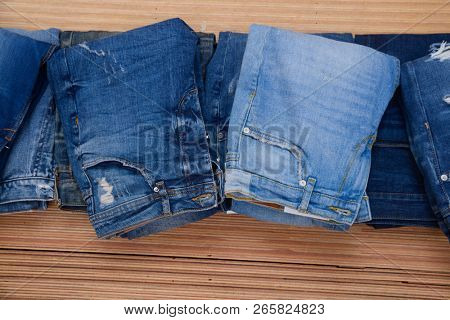 Stylish pile of Blue jeans on a brown wooden background