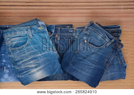 Pil of Jeans. Stylish clothes. Selective focus on wooden background