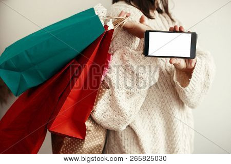 Black Friday. Christmas Sales. Happy Girl Holding Phone With Empty Screen And Carrying Colorful Shop
