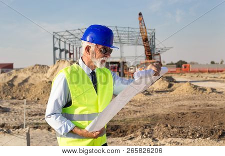 Senior Engineer Looking At Blueprints In Front Of Metal Construction At Building Site