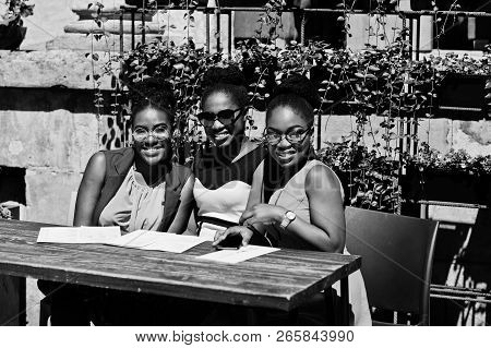 Three Stylish African American Womans Posed At Sunny Summer Day Outdoor, Sitting On Table Of Restaur