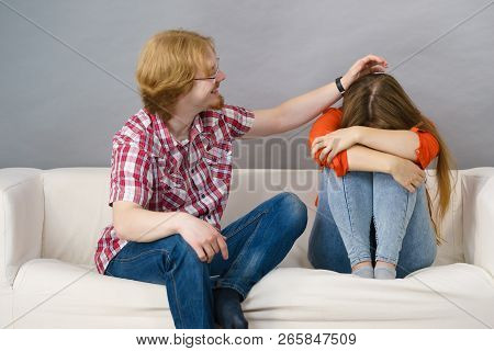 Man Comforting Woman Sitting On Sofa. Friend Confiding To Friend Having A Serious Talk. Couple Solvi