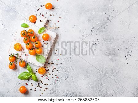 Organic Cherry Orange Rapture Tomatoes On The Vine With Basil And Pepper On Chopping Board On Stone