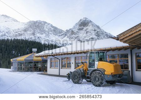 Wheel Loader With Chains On Its Tires, For Plowing Snow, In Winter Alpine Scenery, The Snow-capped A