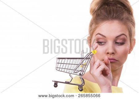 Customer Buying In Shop. Unhappy Thinking Woman Holding Small Tiny Shopping Cart Trolley About To Bu