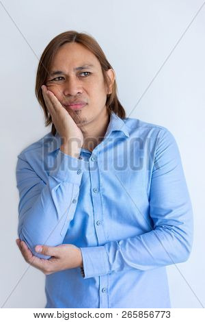 Skeptical Office Worker Feeling Bored. Dull Young Chinese Man In Blue Shirt Leaning Cheek On Hand An