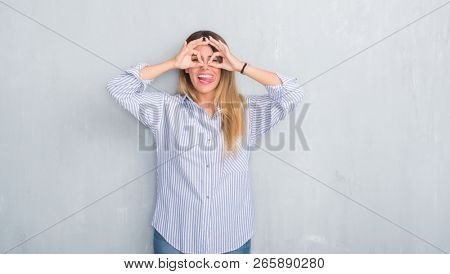 Young adult woman over grey grunge wall wearing fashion business outfit doing ok gesture like binoculars sticking tongue out, eyes looking through fingers. Crazy expression.