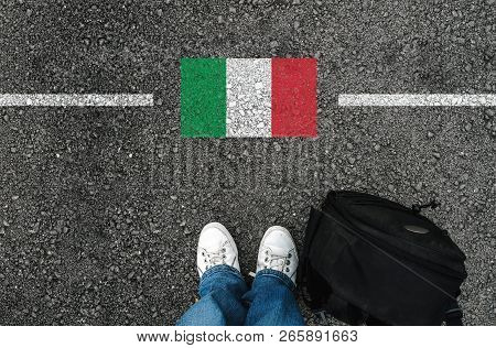 A Man With A Shoes And Backpack Is Standing On Asphalt Nex To Flag Of Italy And Border