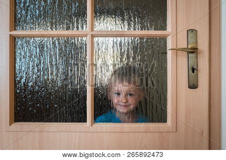 Portrait Of A Cute Little Caucasian Boy Hiding Behind A Door With Glass Windows While Playing Hide A
