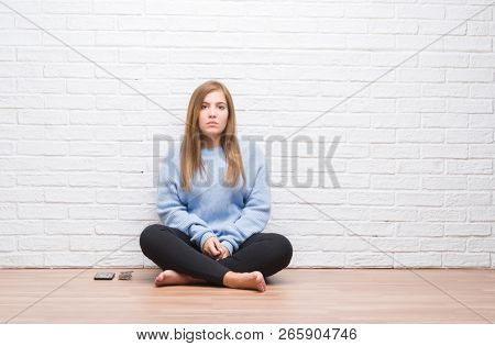 Young adult woman sitting on the floor in autumn over white brick wall with serious expression on face. Simple and natural looking at the camera.