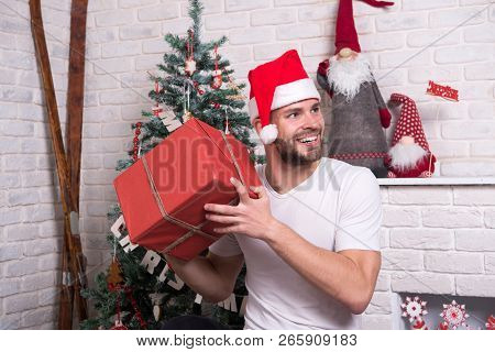 Man In Santa Hat Hold Christmas Present. Online Christmas Shopping. New Year Scene With Tree And Gif