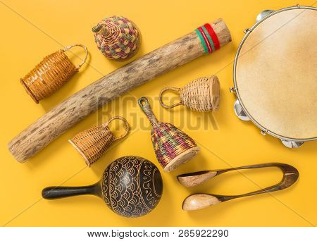 Ethnic Percussion Musical Instruments On Yellow Background. Caxixi Shakers, Rainstick, Pandeiro, Mar