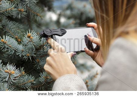 Kharkiv, Ukraine - October 29, 2018:  A young girl photographs the Christmas tree on a macro lens. P