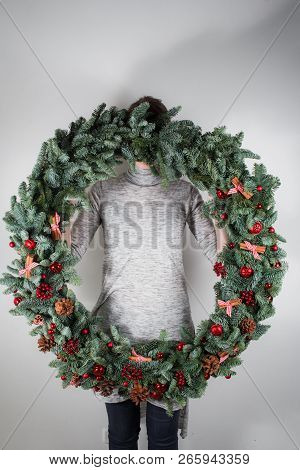 young woman holding christmas large wreath in hands in light, seasonal holidays, rustic theme, adorning poster