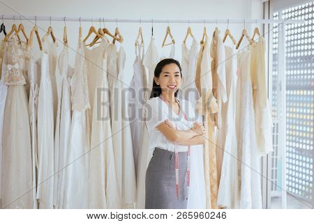 Portrait Of Asian Woman Wedding Dress Store Owner,beautiful Dressmaker In Shop And Small Business