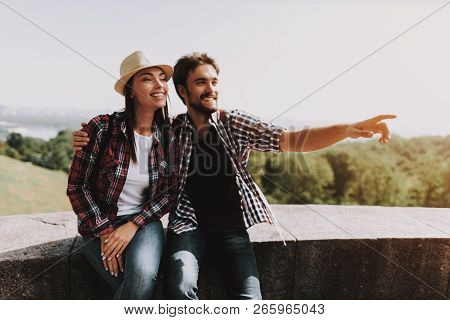 Young Couple Sitting On Ledge And Looking At Park. Young Man And Woman With Backpacks Sitting Togeth