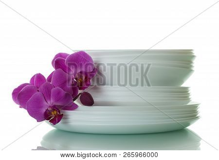 Set Clean Plates And An Orchid Branch Isolated On White Background